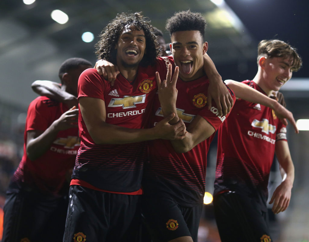 LEIGH, GREATER MANCHESTER - DECEMBER 17:  D'Mani Bughail-Mellor and Mason Greenwood of Manchester United U18s celebrate Di'shon Bernard scoring their third goal during the FA Youth Cup Third Round match between Manchester United U18s and Chelsea U18s at Leigh Sports Village on December 17, 2018 in Leigh, Greater Manchester.