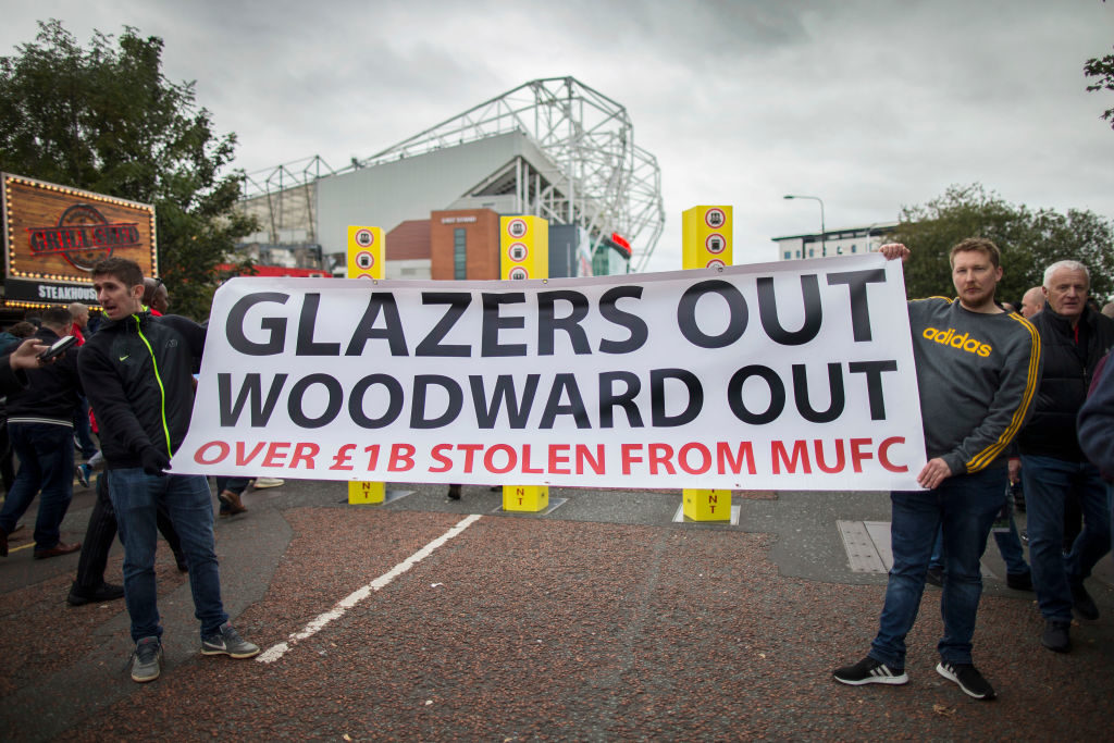 MANCHESTER, ENGLAND - OCTOBER 20: A pair of Man Utd fans hold up a banner against the club's owners, the Glazers, as well as Man Utd Chief Executive Ed Woodward before the Premier League match between Manchester United and Liverpool FC at Old Trafford on October 20, 2019 in Manchester, United Kingdom. Glazer. Protest. United.
