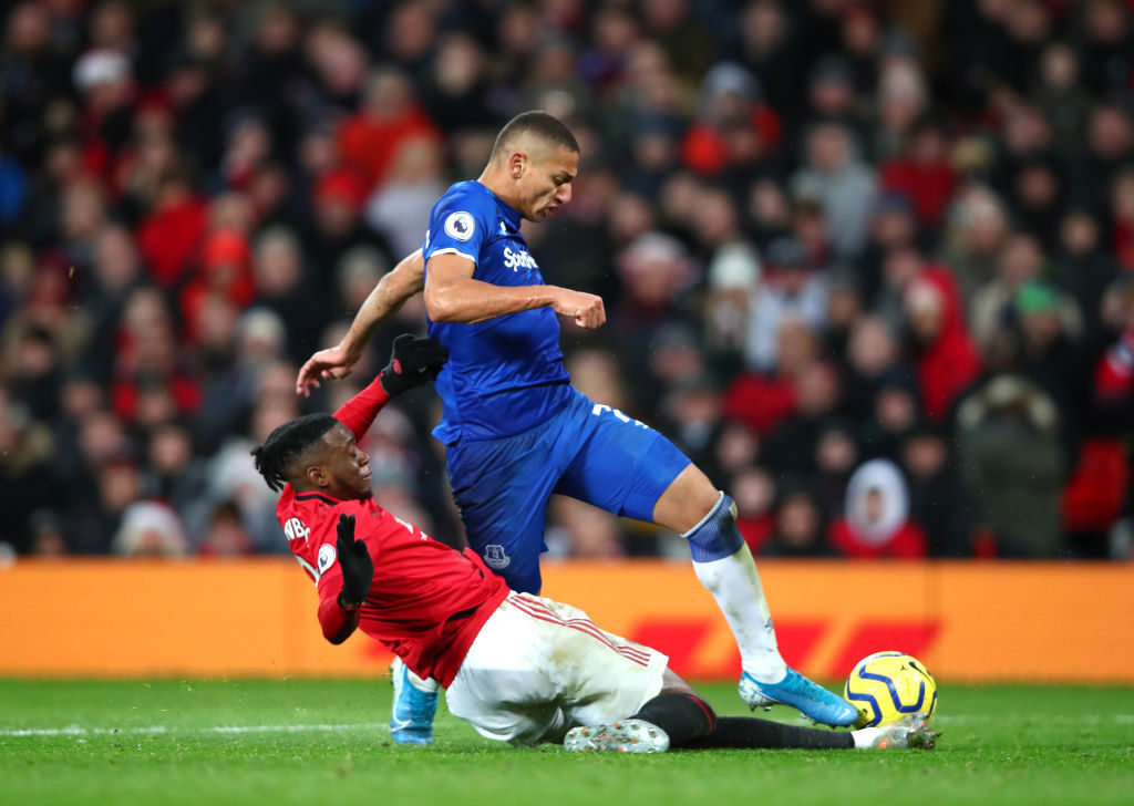 MANCHESTER, ENGLAND - DECEMBER 15: Richarlison of Everton is challenged by full-backs Aaron Wan-Bissaka of Manchester United during the Premier League match between Manchester United and Everton FC at Old Trafford on December 15, 2019 in Manchester, United Kingdom.