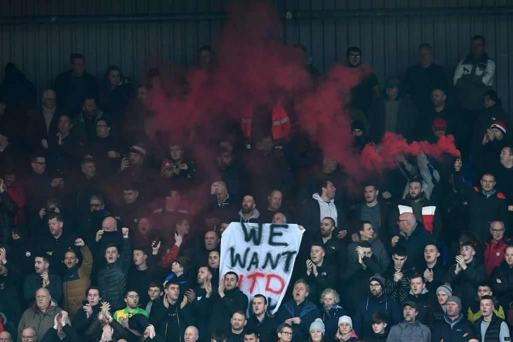 "Manchester United fans hold up a banner stating ""we want utd back"" in the crowd during the English FA Cup fourth round football match between Tranmere Rovers and Manchester United at Prenton Park in Birkenhead, north west England, on January 26, 2020. (Photo by Paul ELLIS / AFP) / RESTRICTED TO EDITORIAL USE. No use with unauthorized audio, video, data, fixture lists, club/league logos or 'live' services. Online in-match use limited to 120 images. An additional 40 images may be used in extra time. No video emulation. Social media in-match use limited to 120 images. An additional 40 images may be used in extra time. No use in betting publications, games or single club/league/player publications. Glazer protest United. Ed Woodward."