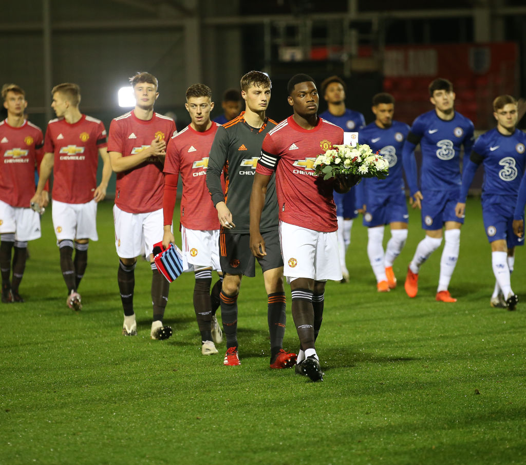 BURTON-UPON-TRENT, ENGLAND - OCTOBER 30: Teden Mengi of Manchester United U18s leads the team out, carrying a wreath in honour of Jeremy Wisten and Nobby Stiles, ahead of the FA Youth Cup semi-final match between Manchester United U18s and Chelsea U18s at St Georges Park on October 30, 2020 in Burton-upon-Trent, England.