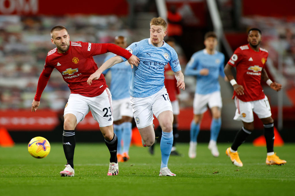 MANCHESTER, ENGLAND - DECEMBER 12: Luke Shaw of Manchester United and Kevin De Bruyne of Manchester City  battle for the ball  during the Premier League match between Manchester United and Manchester City at Old Trafford on December 12, 2020 in Manchester, England. The match will be played without fans, behind closed doors as a Covid-19 precaution.