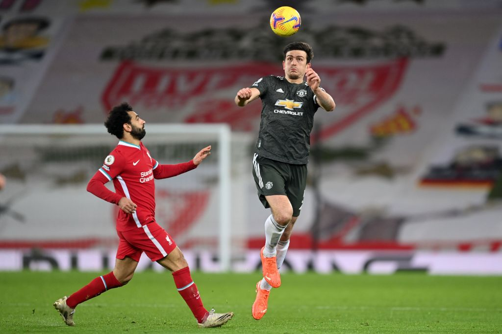 Manchester United's English defender Harry Maguire (C) jumps to head the ball as Liverpool's Egyptian midfielder Mohamed Salah (L) closes in during the English Premier League football match between Liverpool and Manchester United at Anfield in Liverpool, north west England on January 17, 2021. (Photo by Michael Regan / POOL / AFP) / RESTRICTED TO EDITORIAL USE. No use with unauthorized audio, video, data, fixture lists, club/league logos or 'live' services. Online in-match use limited to 120 images. An additional 40 images may be used in extra time. No video emulation. Social media in-match use limited to 120 images. An additional 40 images may be used in extra time. No use in betting publications, games or single club/league/player publications. /