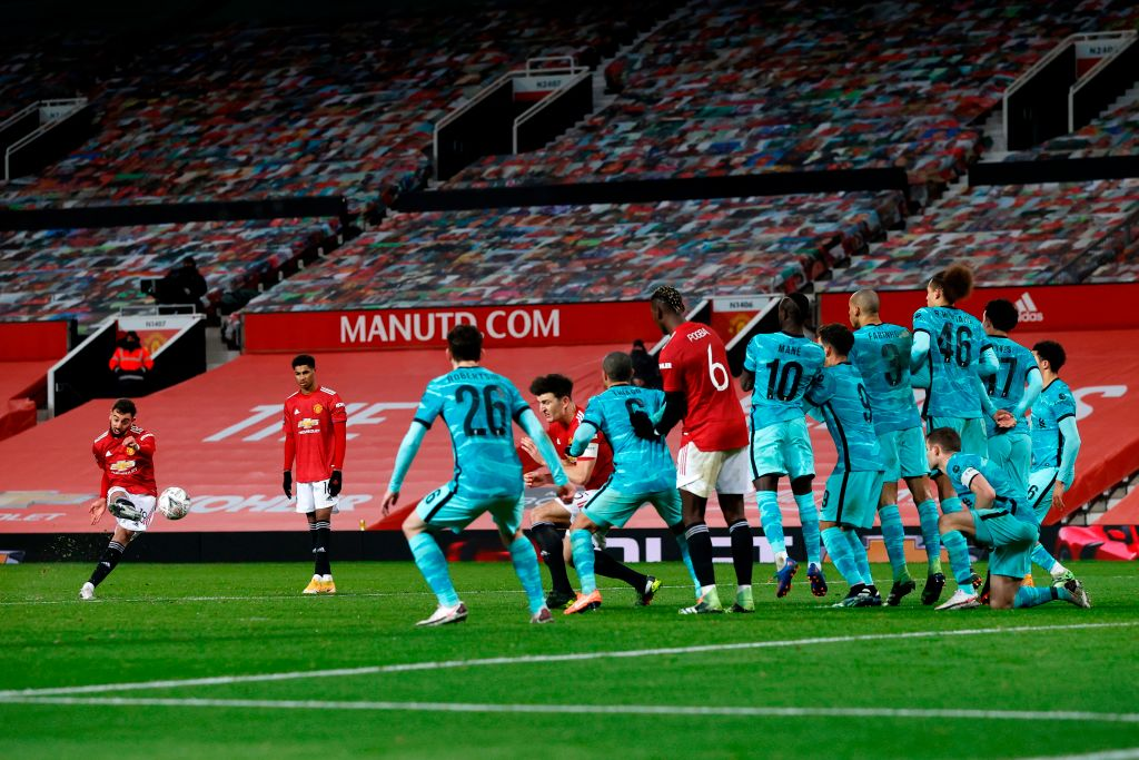 Manchester United's Portuguese midfielder Bruno Fernandes (L) shoots to score from a free kick for their third goal during the English FA Cup fourth round football match between Manchester United and Liverpool at Old Trafford in Manchester, north west England, on January 24, 2021. (Photo by PHIL NOBLE / POOL / AFP)