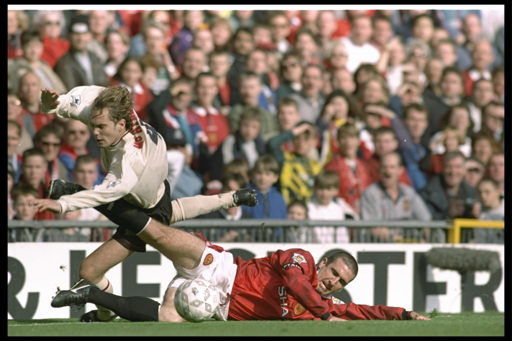 Jason McAteer of Liverpool (left) is brought down by Eric Cantona of Manchester United