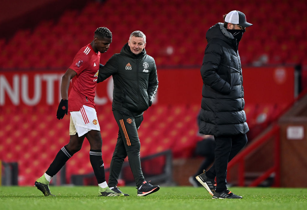 MANCHESTER, ENGLAND - JANUARY 24: Paul Pogba of Manchester United and Ole Gunnar Solskjær, Manager of Manchester United interact as Jurgen Klopp, Manager of Liverpool makes their way across the pitch after The Emirates FA Cup Fourth Round match between Manchester United and Liverpool at Old Trafford on January 24, 2021 in Manchester, England.
