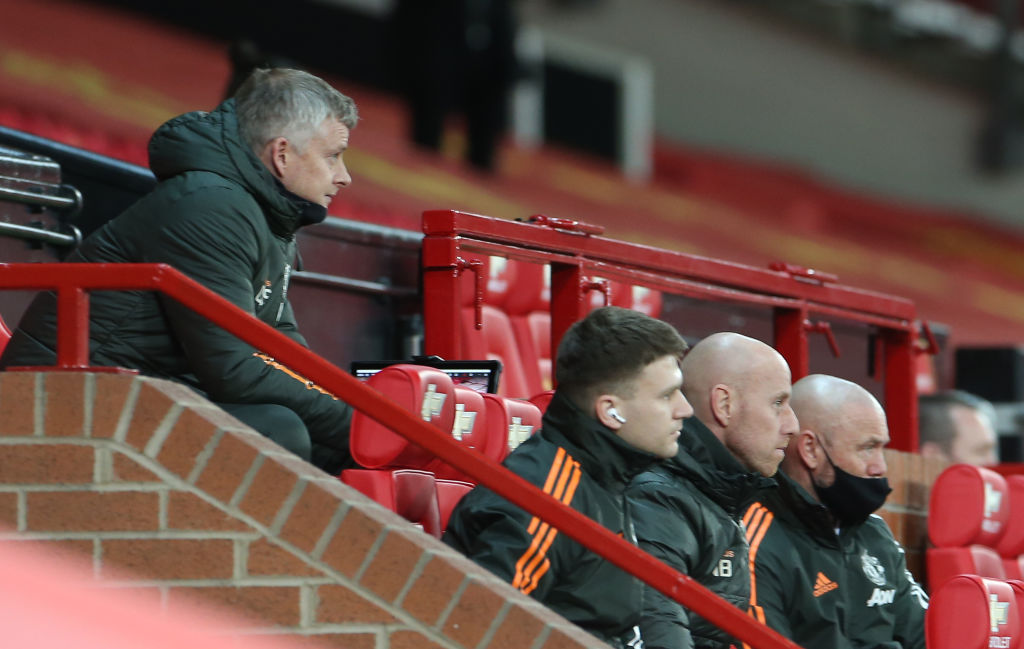 MANCHESTER, ENGLAND - FEBRUARY 21: Manager Ole Gunnar Solskjaer of Manchester United watches from the dugout duringthe Premier League match between Manchester United and Newcastle United at Old Trafford on February 21, 2021 in Manchester, England.