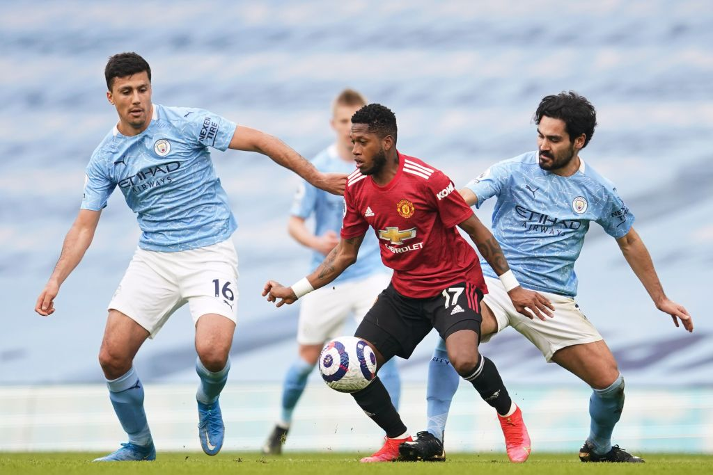 Manchester United's Brazilian midfielder Fred (C) is surrounded by Manchester City's German midfielder Ilkay Gundogan (R) and Manchester City's Spanish midfielder Rodrigo (L) during the English Premier League football match between Manchester City and Manchester United at the Etihad Stadium in Manchester, north west England, on March 7, 2021.