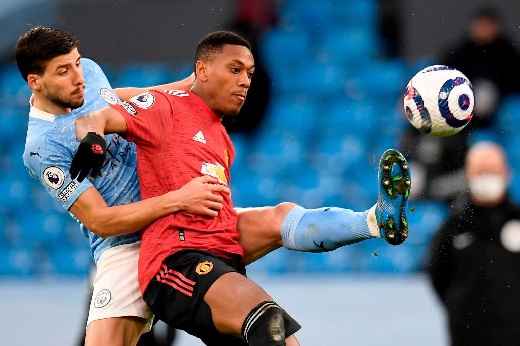 Manchester City's Portuguese defender Ruben Dias (L) vies with Manchester United's French striker Anthony Martial (R) during the English Premier League football match between Manchester City and Manchester United at the Etihad Stadium in Manchester, north west England, on March 7, 2021. (Photo by PETER POWELL / POOL / AFP) / RESTRICTED TO EDITORIAL USE.