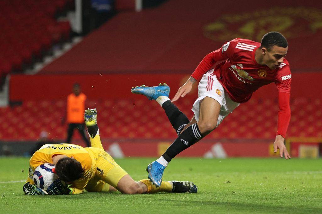 West Ham United's Polish goalkeeper Lukasz Fabianski (L) reaches the ball ahead of Manchester United's English striker Mason Greenwood (R) during the English Premier League football match between Manchester United and West Ham United at Old Trafford in Manchester, north west England, on March 14, 2021.