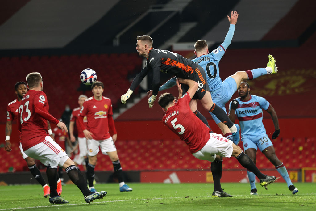 MANCHESTER, ENGLAND - MARCH 14: Dean Henderson of Manchester United punches the ball away as he collides with team mate Harry Maguire and Jarrod Bowen of West Ham United during the Premier League match between Manchester United and West Ham United at Old Trafford on March 14, 2021 in Manchester, England.