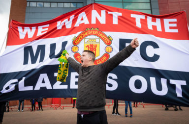 A football fan chants slogans in front of a banner before a
